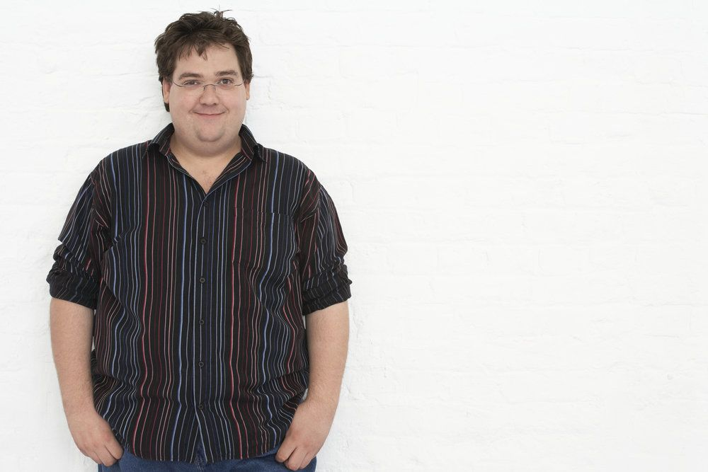 An overweight man in a white room