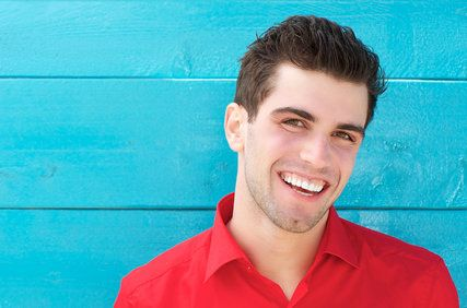 Smiling man in red shirt posing against turquoise building