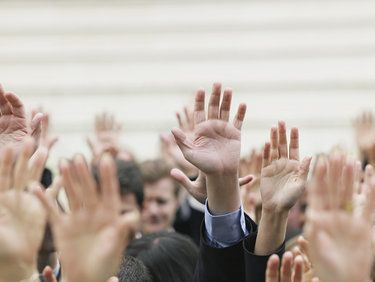 Crown of businessmen raising their hand