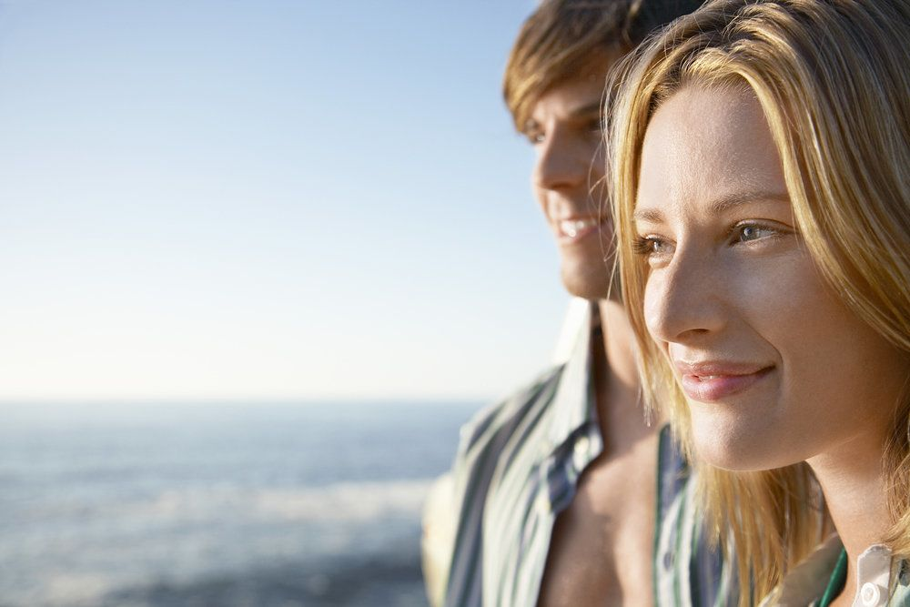 A woman standing in front of her boyfriend as they stand beside the ocean, her eyes focused on the horizon after LASIK surgery
