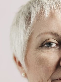 Smiling middle-aged woman posing against white background