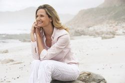 Woman sitting on beach smiling