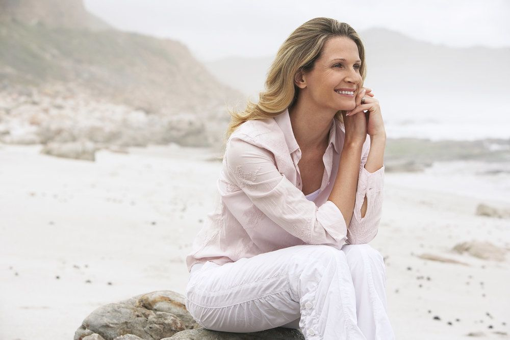 Woman sitting on beach smiling