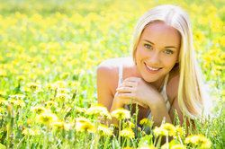 Beautiful young woman in a clearing among the flowers.