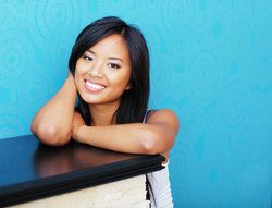 Portrait of a young beautiful Asian woman over blue background