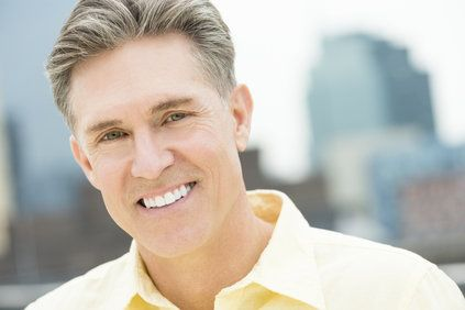 Smiling man with gray hair wearing light yellow shirt