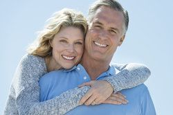 Middle-aged couple smiling broadly, showing off their healthy teeth