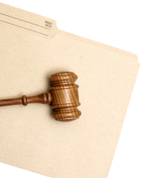 Wooden gavel resting on manila envelope