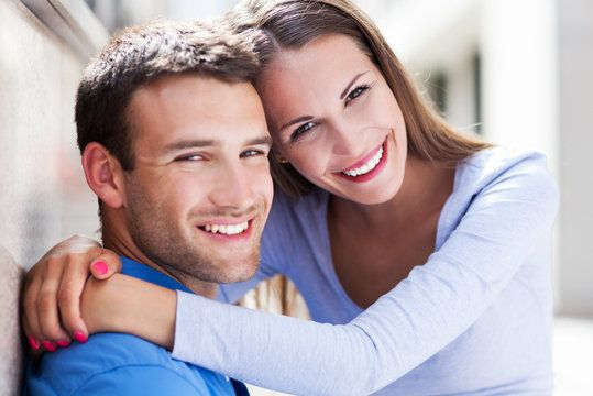 Attractive couple posing with woman sitting in man's lap