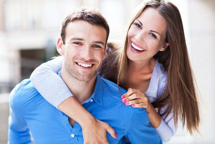 Smiling couple with man piggybacking woman