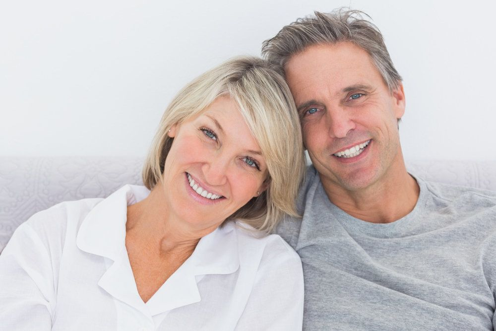 Calm, smiling couple with beautiful teeth on gray background.