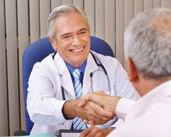 A physician smiling and shaking hands with a patient after explaining colonoscopy prep to him