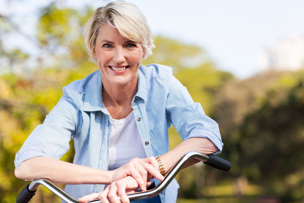A middle-aged female patient on a bicycle, smiling to reveal her healthy teeth and gums, suggesting good dental health and heart health