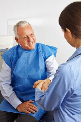 An older male patient shaking hands with a dentist