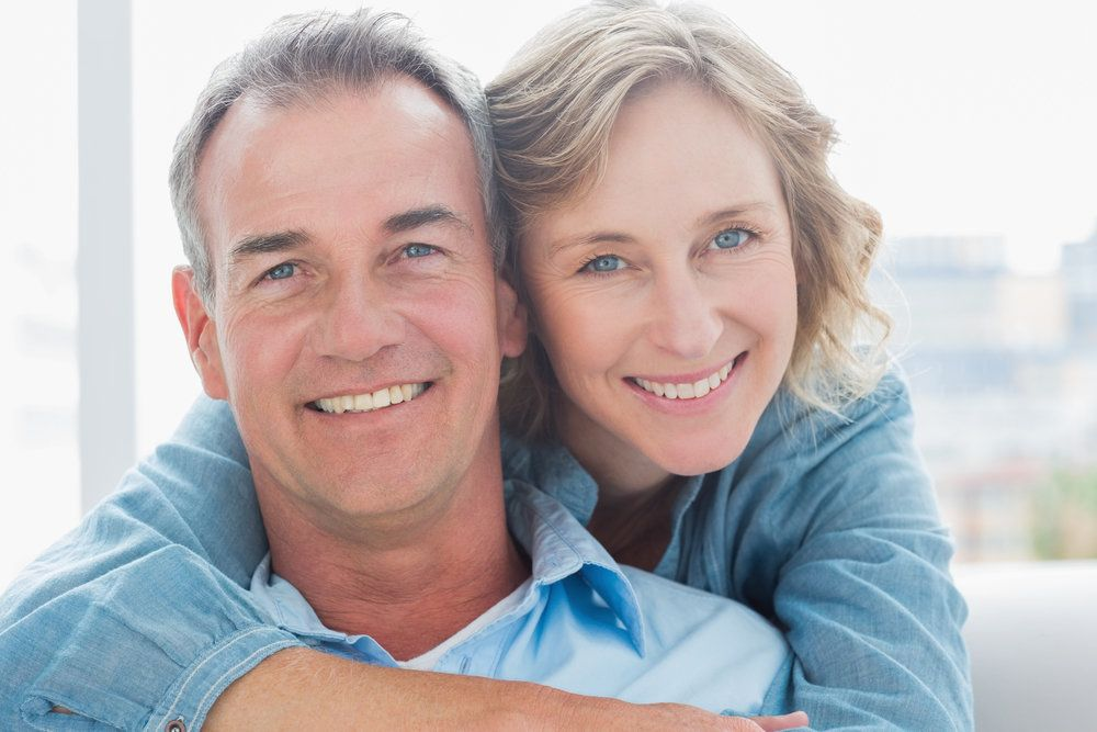 Happy-looking couple with woman hugging man from behind