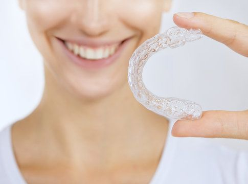 Smiling woman holding clear aligner tray
