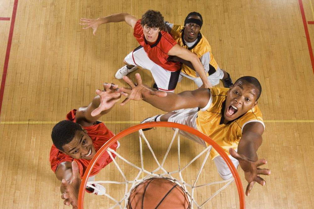 A group of basketball players under the net, including one who just underwent LASIK