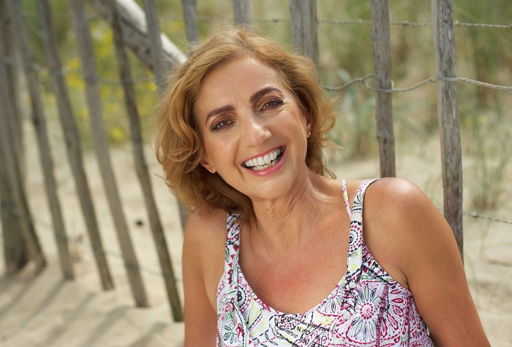 A beautiful middle-aged woman poses in front of wooden posts lining a beach.