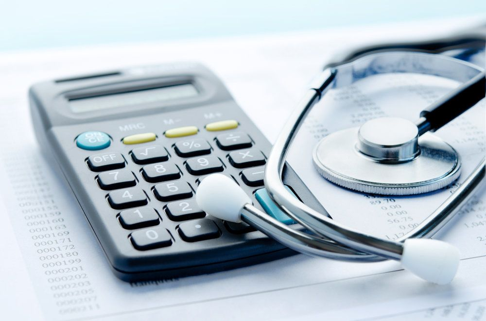 A calculator and stethoscope on a medical bill