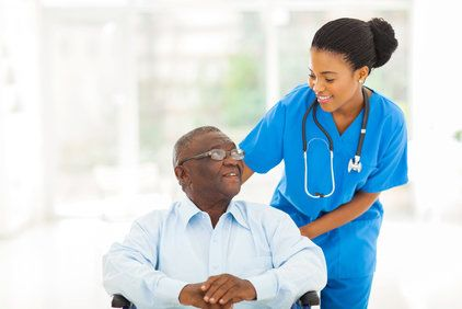 A man sitting down looks up happily at his nurse.