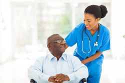 Elderly African American man in wheelchair receiving assistance from a nurse