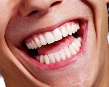Extreme close-up of man's very straight, white teeth
