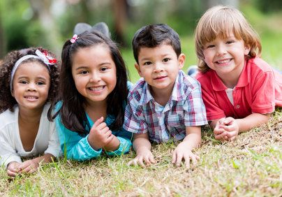 Four smiling kids lying on stomachs in field