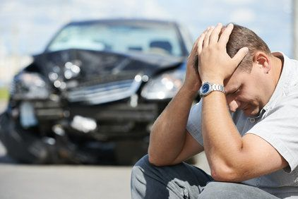 A man with his head in his hands after an auto accident