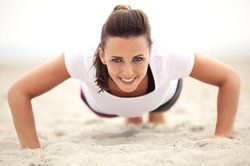 A woman doing push-ups on the beach