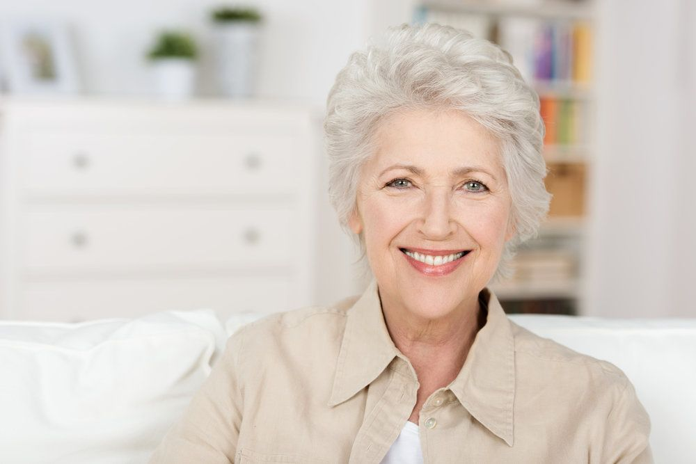 A grey-haired woman smiling on the couch