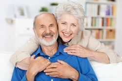 An older couple in an embrace, content that their dental health is not affected by smoking