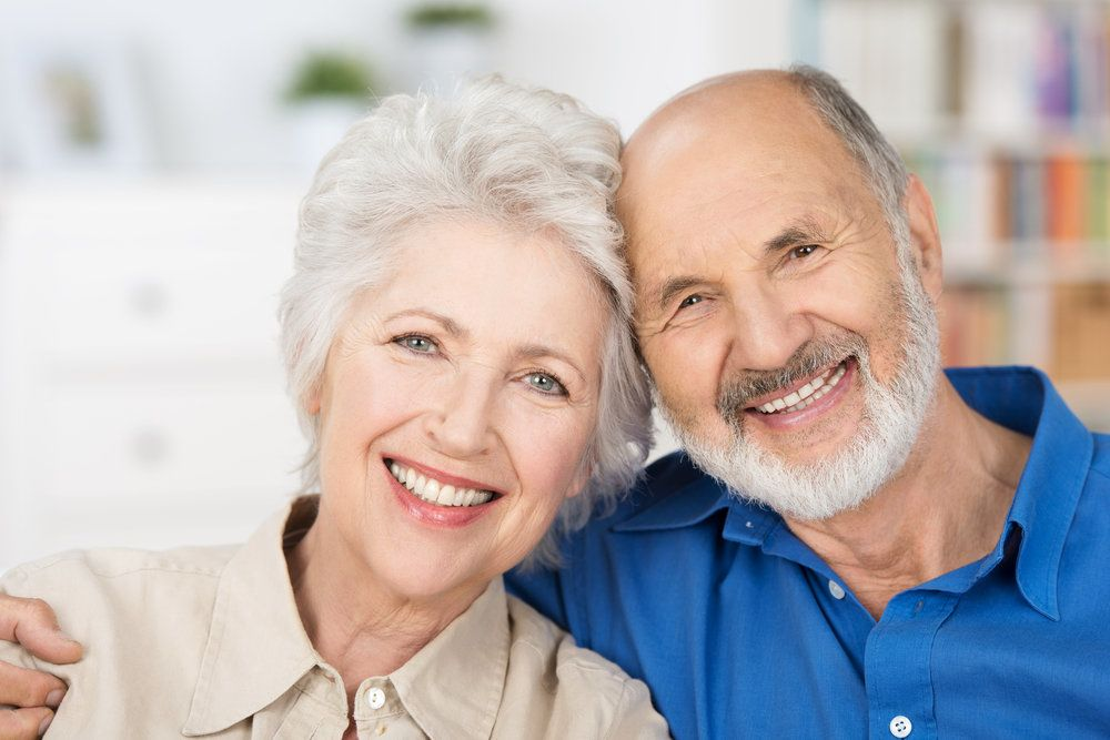 An elderly man and woman both with a full set of white, healthy teeth