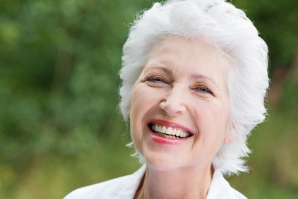 Smiling elderly woman with white hair and bright red lipstick