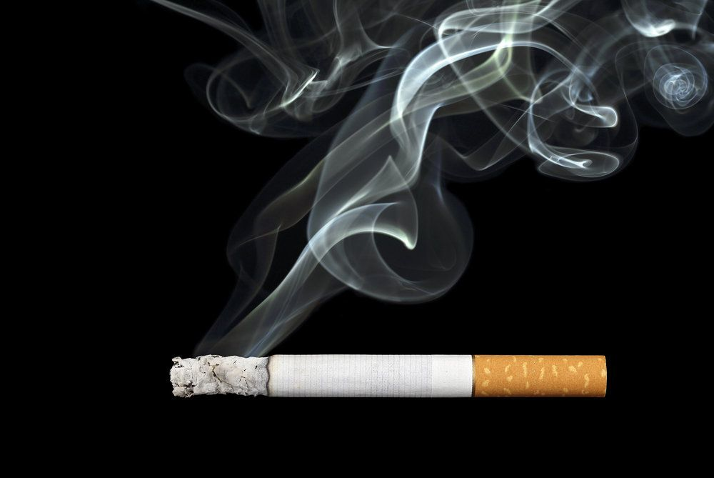 Close-up of a lit cigarette, which can seriously and negatively affect a person's oral health