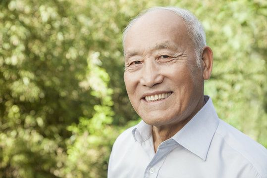 Smiling, elderly Asian American man in collared shirt