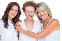 Three women of differing ages pose together, smiling brightly.