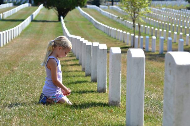 young girl praying at grave in a cemetery