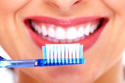 Woman smiling broadly while holding a new toothbrush up to her mouth