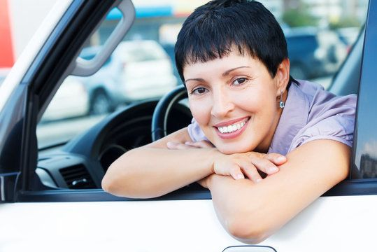 Woman smiling while sitting in a car