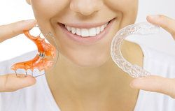 Smiling woman holding retainer and clear aligner