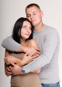 Man hugging wistful-looking woman from behind
