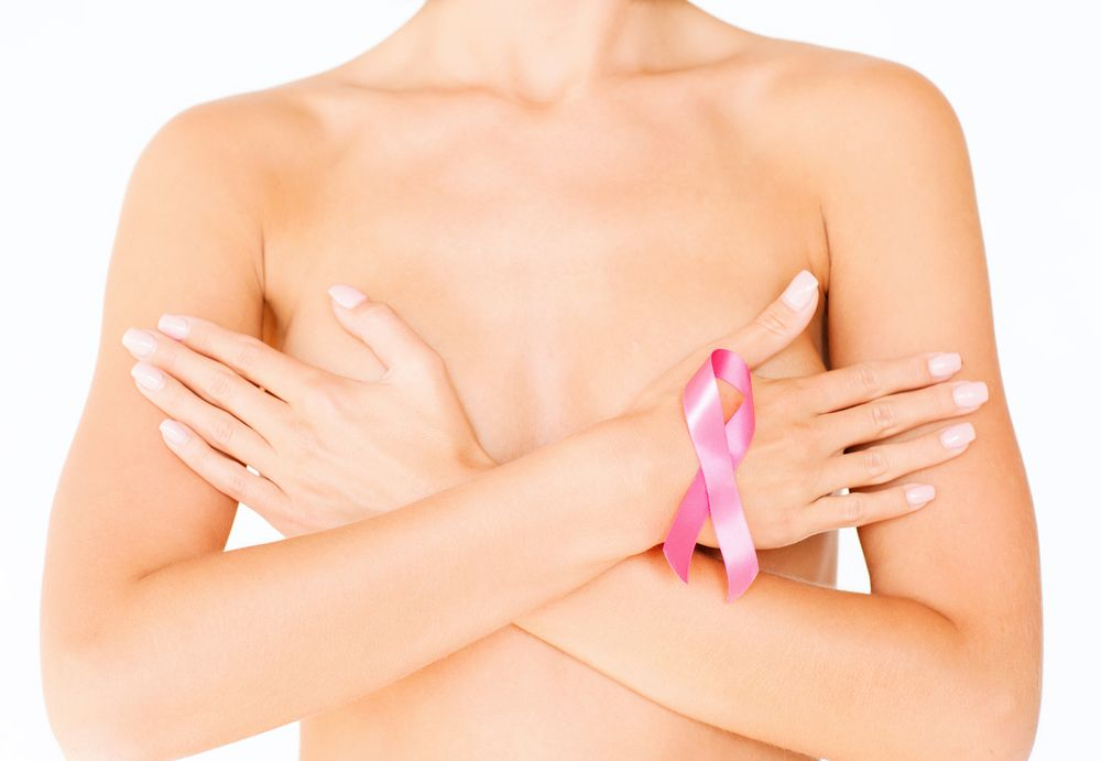Topless woman crossing arms over breasts and wearing breast cancer awareness ribbon