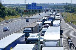 Large commercial trucks traveling on a highway, creating a heightened risk for auto accidents