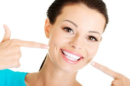 Woman with very white teeth pointing to her smile