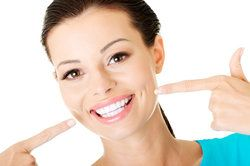 Woman pointing at her straight white teeth