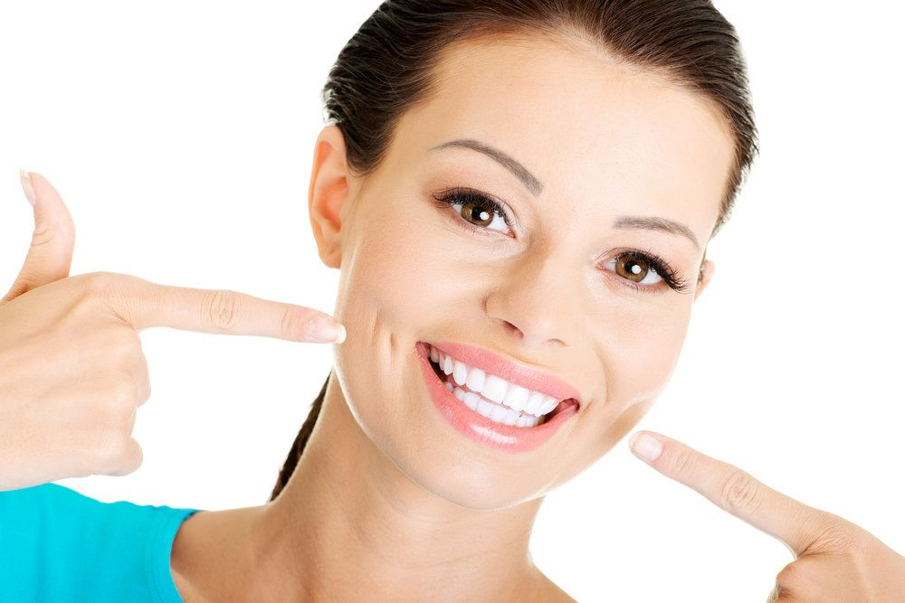 Brunette woman pointing at her white teeth.
