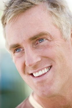 A close-up three-quarters profile of a mature man with greying blond hair and a smile featuring porcelain veneers