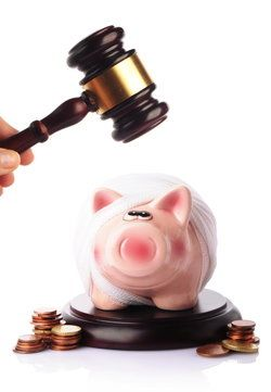A judge's gavel, held above a piggy bank