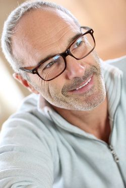 A middle-aged bespectacled man, smiling and looking as though he can see the world quite clearly