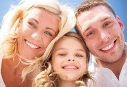 Smiling couple with young girl looking down at camera